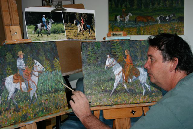 Leigh works on canvases side-by-side